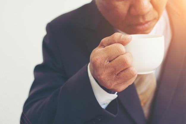 Unternehmer, die eine tasse kaffee auf weißem hintergrund isoliert