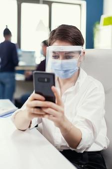Unternehmer, die gesichtsmaske als sicherheitsvorkehrung gegen covid 19 tragen, die auf dem smartphone am arbeitsplatz chatten. multiethnische mitarbeiter, die in finanzunternehmen unter wahrung der sozialen distanz arbeiten. neue normalität.
