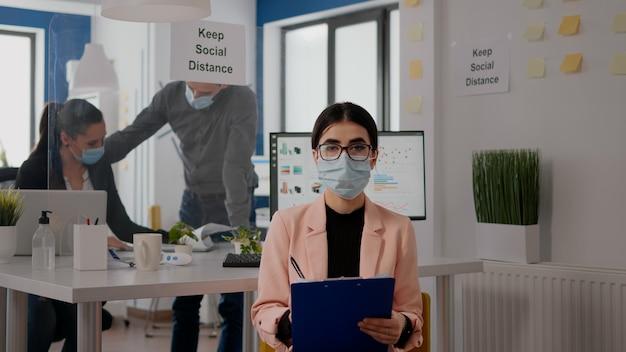 Unternehmer, die in einem neuen normalen büro sitzen und in die kamera schauen, während sie lifestyle-informationen während eines online-videoanrufs schreiben. geschäftsfrau, die gesichtsmaske trägt, um eine infektion mit covid19 zu vermeiden