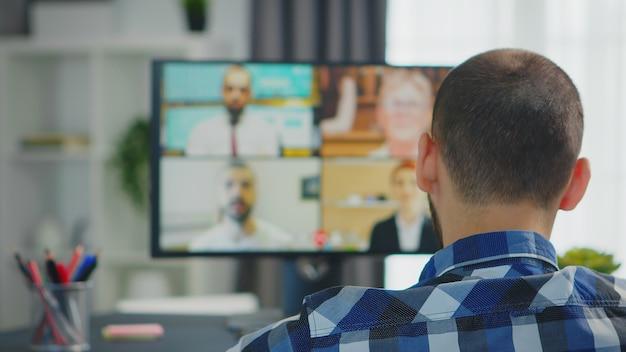 Unternehmer im rollstuhl im chat mit kollegen in einer videokonferenz.