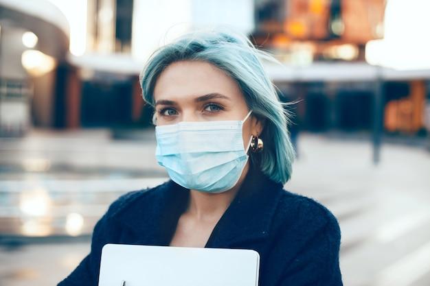 Unternehmer mit blauen haaren trägt eine schutzmaske, während er draußen mit dem computer posiert