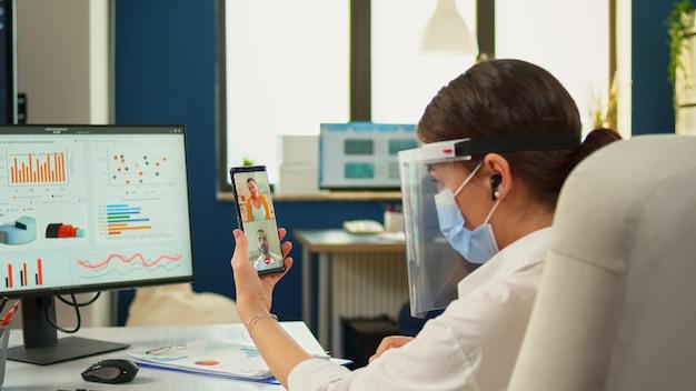 Unternehmer mit gesichtsmaske, die per videoanruf mit dem unternehmensleiter und dem leitenden administrator über smartphone und headset spricht. multiethnische mitarbeiter, die in der wirtschaft mit respekt vor der sozialen distanz arbeiten