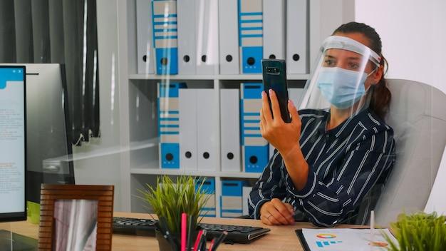 Unternehmer mit gesichtsschutz gegen coronavirus mit telefon für videomeetings im gespräch mit remote-mitarbeitern, die in einem neuen normalen bürogebäude sitzen. frau respektiert soziale distanz