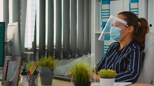 Unternehmer mit maske während der coronavirus-pandemie, die in einem neuen normalen geschäftsbüro arbeitet und mit einem mitarbeiter diskutiert, der finanzdaten analysiert. freiberufler, der soziale distanz in unternehmen respektiert.
