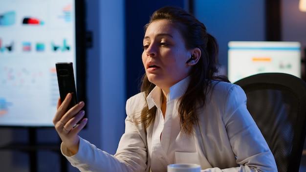 Unternehmer mit virtuellem meeting mit smartphone mit drahtlosem kopfhörer am schreibtisch am arbeitsplatz. freiberufler, der mit remote-team-chat virtuelle online-konferenz über das internet arbeitet