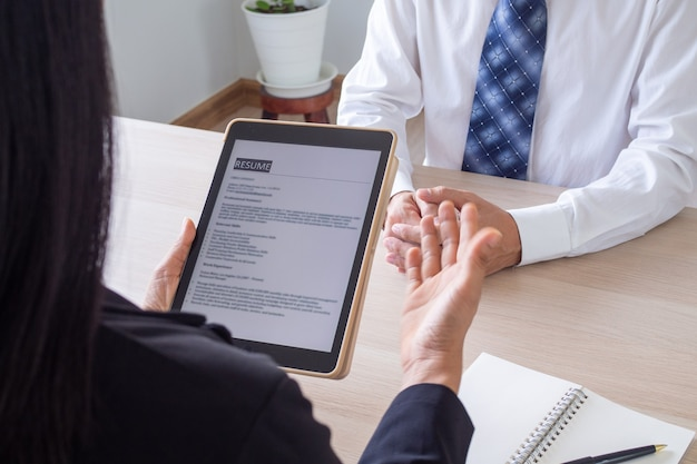 Unternehmer öffnen den lebenslauf für den bewerber in einer e-mail per tablet während eines vorstellungsgesprächs. beschäftigungskonzept