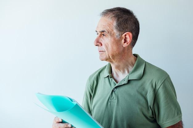 Unternehmer pensionierter mann, der ein grünes hemd hält, das einen ordner mit einem bericht hält