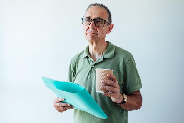 Unternehmer pensionierter mann, der ein grünes hemd und eine brille trägt, einen ordner mit einem bericht und einem kaffee hält, denkt