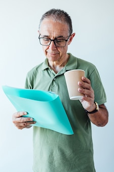 Unternehmer pensionierter mann, der ein grünes hemd und eine brille trägt und einen ordner mit einem bericht und einem kaffee hält