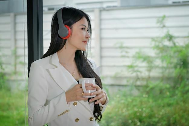 Unternehmer, schöne frau, die kaffee trinkt und musik während der mittagspausen hört