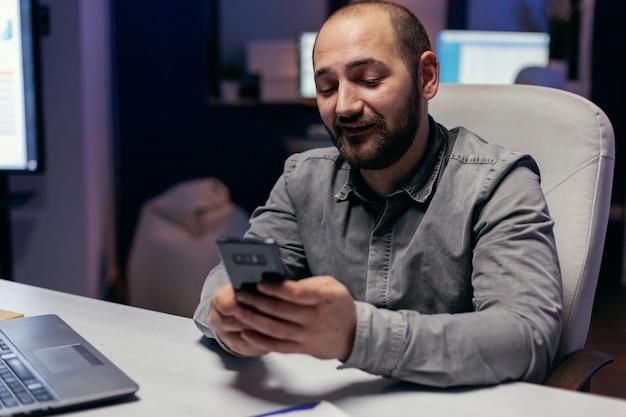 Unternehmer schreiben text auf dem smartphone, das am schreibtisch an einem leeren arbeitsplatz sitzt. geschäftsmann, der seine zelle verwendet, um eine sms zu senden, während er spät nachts im büro arbeitet, um eine frist zu beenden.