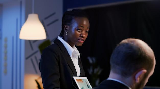 Unternehmer schwarze frau erklärt managementstrategie mit tablet über statistiken. business vielfältige multiethnische teamarbeit, die spät in der nacht im besprechungsraum des unternehmensbüros arbeitet