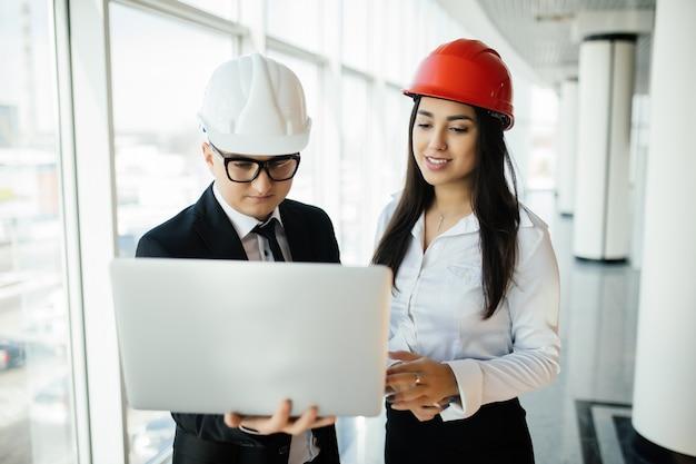 Unternehmer und architektin der frau und des mannes in hemlet beim geschäftstreffen, das den laptop auf bauplänen betrachtet