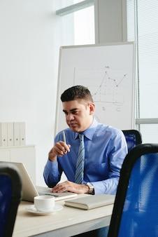 Unternehmer von mittlerem alter, der e-mail auf seinem laptop überprüft