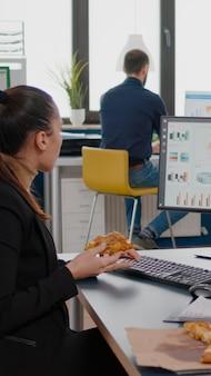 Unternehmerfrau, die essenspause am tisch sitzt und pizzascheiben-fastfood-lieferung isst. lunchpaket zum mitnehmen, das im firmenbüro geliefert wird. essen zum mitnehmen zur mittagszeit essen am schreibtisch