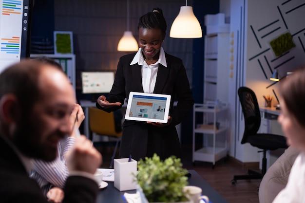 Unternehmerfrau, die im besprechungsraum des unternehmensbüros überarbeitet und die managementstrategie mit tablet erklärt