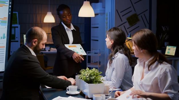 Unternehmerfrau mit dunkler haut, die im besprechungsraum des unternehmensbüros überarbeitet