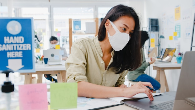 Unternehmerin aus asien, die eine medizinische gesichtsmaske für soziale distanzierung in einer neuen normalen situation zur virenprävention trägt, während sie den laptop wieder bei der arbeit im büro verwendet. leben und arbeiten nach dem coronavirus.