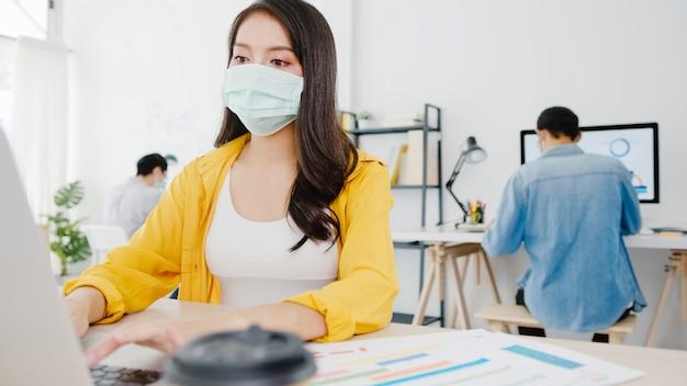 Unternehmerin aus asien, die eine medizinische gesichtsmaske für soziale distanzierung in einer neuen normalen situation zur virenprävention trägt, während sie den laptop wieder bei der arbeit im büro verwendet. lebensstil nach dem koronavirus.