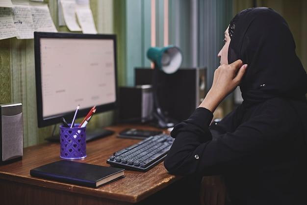 Unternehmerin aus dem nahen osten. beschäftigte arabische geschäftsfrau. frau in traditioneller arabischer kleidung hijab oder abaya, die am pc arbeitet