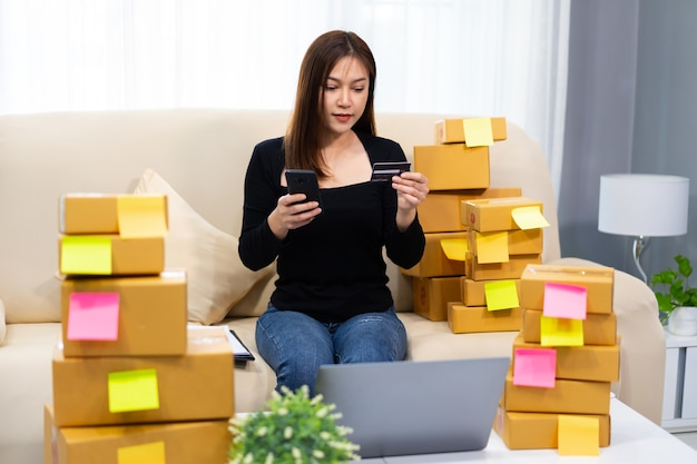 Unternehmerin, die ein smartphone mit kreditkarte im heimbüro verwendet