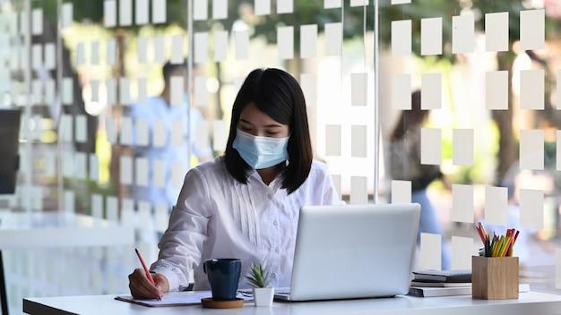 Unternehmerin, die gesichtsmaske trägt, während sie an einem computer arbeitet und notizen im modernen büro schreibt.