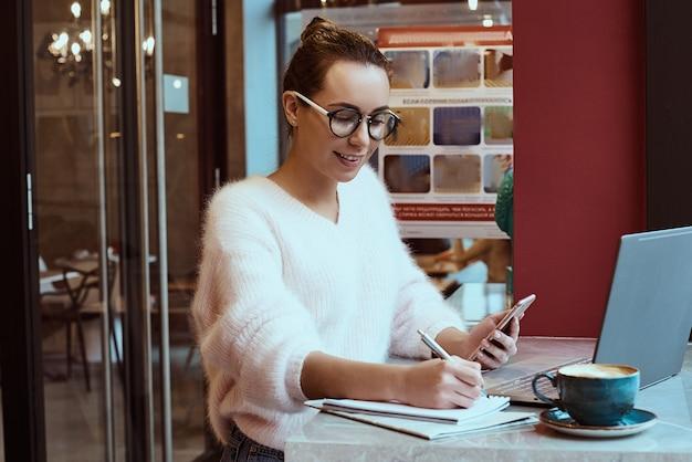 Unternehmerin, die vom café arbeitet und am handy mit kopfhörern spricht