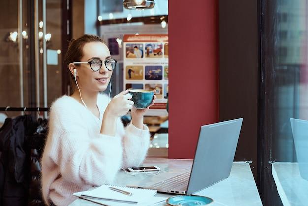 Unternehmerin, die vom café arbeitet und am handy spricht