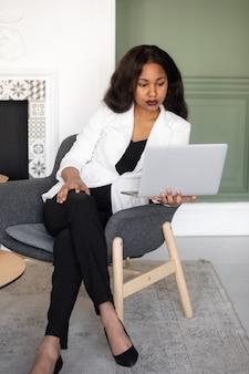 Unternehmerin fröhliche afroamerikanische geschäftsfrau, die am laptop im modernen büro arbeitet