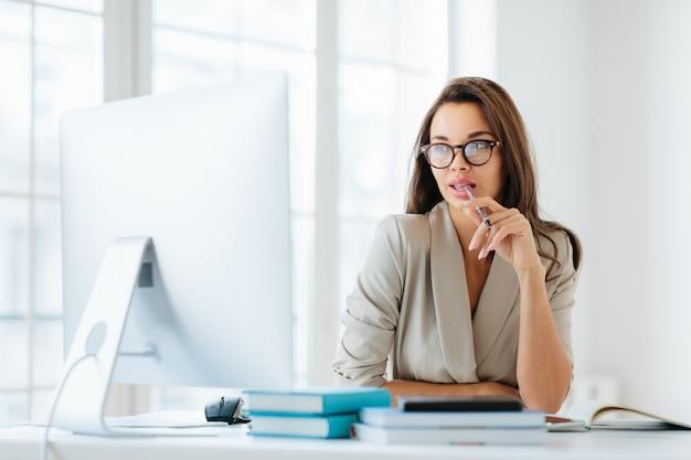 Unternehmerin hält stift im mund, im monitor des computers konzentriert
