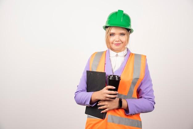 Unternehmerin in schutzhelm mit zwischenablage und schwarzer tasse auf weiß.