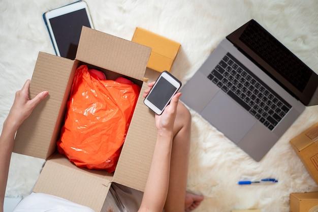 Unternehmerin-inhaber kmu-geschäft überprüft bestellung mit smartphone, laptop und verpackungskasten, um ihren kunden zu senden