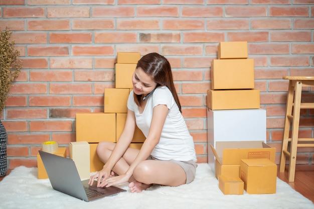 Unternehmerin inhaber kmu geschäft überprüft bestellung mit telefon, laptop und verpackungsbox, um ihren kunden zu senden