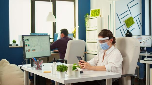 Unternehmerin mit schutzmaske, die im professionellen arbeitsbereich arbeitet und auf dem handy vor dem computer tippt. multiethnische mitarbeiter, die in finanzunternehmen unter wahrung der sozialen distanz arbeiten
