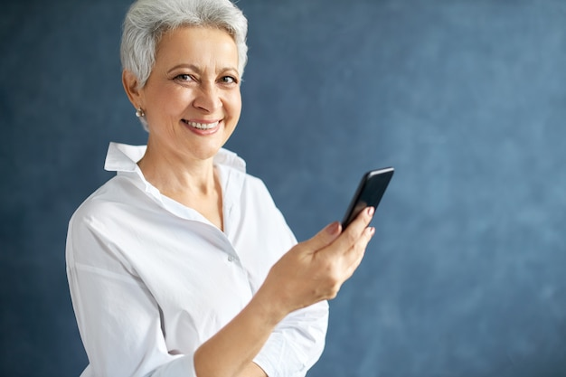 Unternehmerin mittleren alters mit kurzen grauen haaren, die handy halten, geschäftliche anrufe tätigen, textnachricht schreiben.