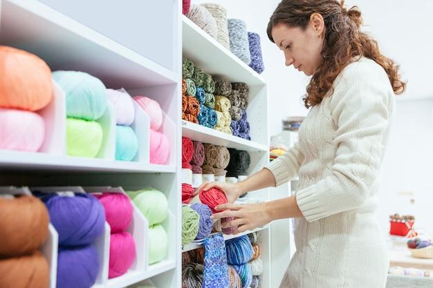 Unternehmerische frau in ihrem eigenen einzelhandelsgeschäft, die wollgarne aufhebt
