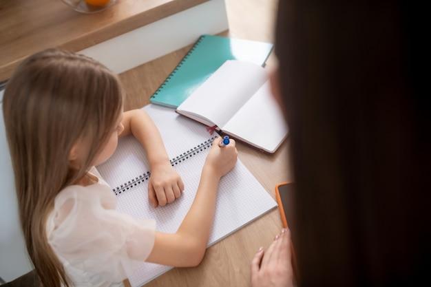 Unterricht. ein langhaariges mädchen, das zu hause lernt und involviert aussieht