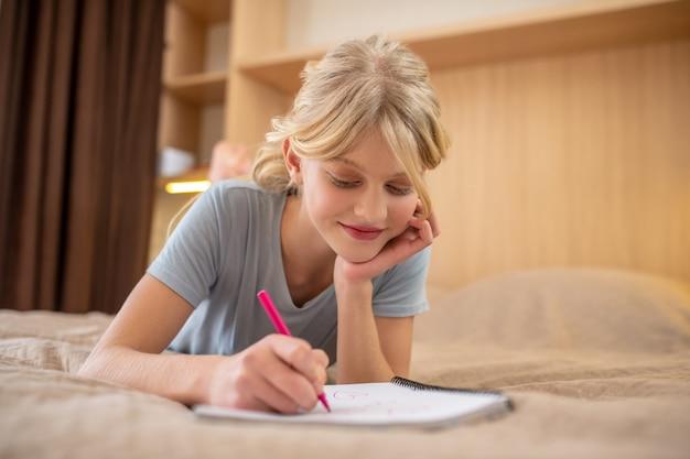 Unterricht machen. ein mädchen liegt auf dem bett und schreibt etwas in ein notizbuch