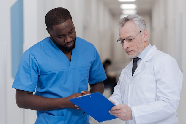 Unterrichte meinen praktikanten. alternder professioneller positiver arzt, der im krankenhaus steht, während ordner hält und afroamerikanerpraktikant konsultiert
