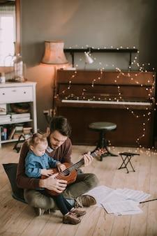 Unterrichtende tochter des vaters, zum der gitarre im raum zu hause zu spielen