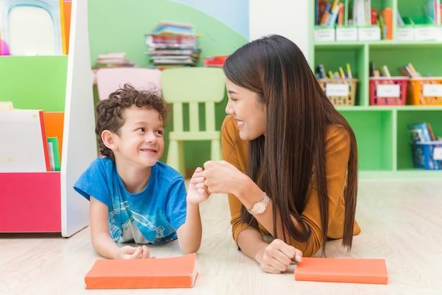 Unterrichtender amerikaner des jungen asiatischen frauenlehrers im kindergartenklassenzimmer mit glück und entspannung. bildung, grundschule, lernen und leutekonzept - lehrerhilfeschule scherzt klassenzimmer.