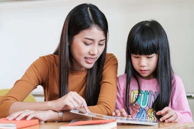 Unterrichtendes mädchen des jungen asiatischen frauenlehrers im kindergartenklassenzimmer