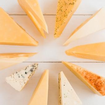 Unterschiedliche art des dreieckigen käses vereinbarte im rundschreiben auf weißem schreibtisch