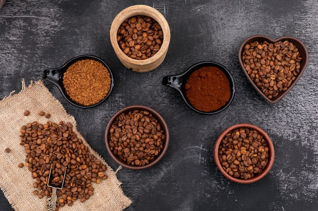 Unterschiedliche art des kaffees in der keramischen hölzernen schüssel auf schwarzer holzoberfläche
