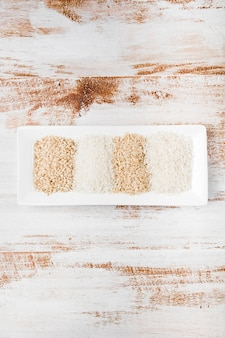 Unterschiedliche art des ungekochten reises im weißen kleinen behälter auf rustikalem hintergrund