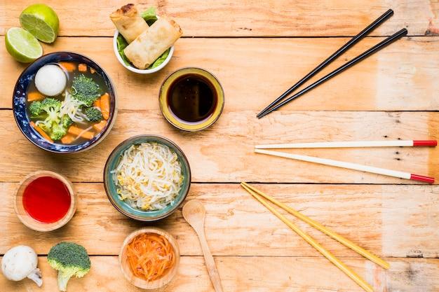 Unterschiedliche art von essstäbchen mit thailändischem traditionellem köstlichem lebensmittel auf hölzernem schreibtisch