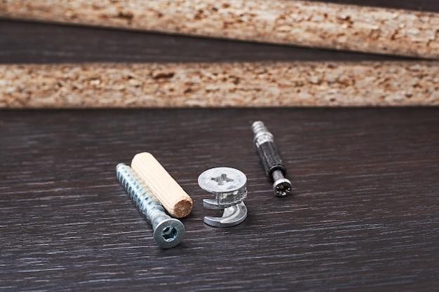 Unterschiedliche art von möbelmontagewerkzeugen, -exzenter und -euroschraube an einem hölzernen hintergrund