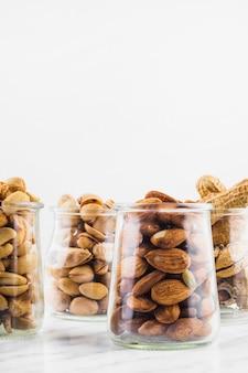 Unterschiedliche art von nussnahrungsgläsern auf marmoroberfläche