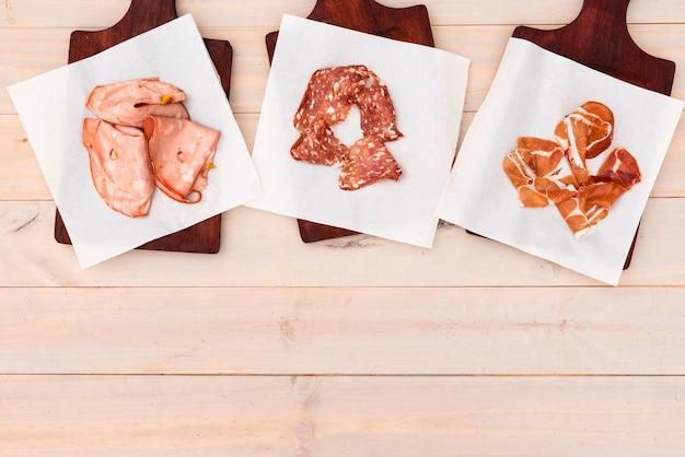 Unterschiedlicher italienischer schinken und salami auf schneidebrett über tabelle