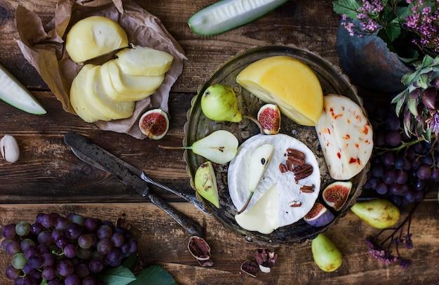 Unterschiedlicher käse, frische früchte und gartenblumen auf altem hölzernem hintergrund.